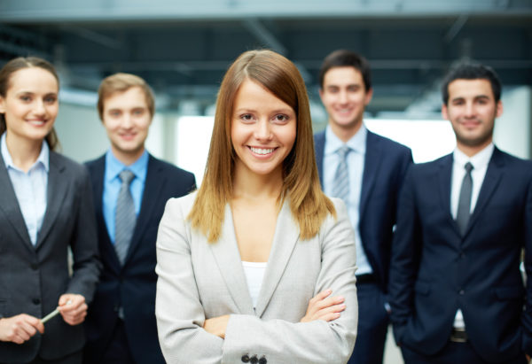 Group of friendly businesspeople with happy female leader in front